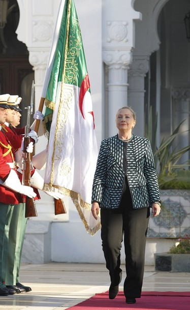 U.S. Secretary of State Hillary Clinton inspects an honour guard during a welcoming ceremony at the presidential palace in Algiers