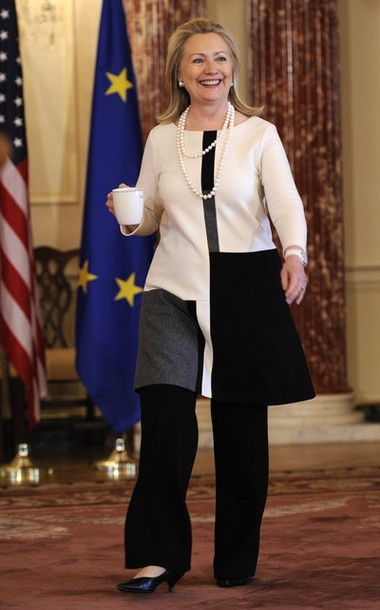 US Secretary of State Hillary Clinton carries a cup as she arrives to discuss the just-concluded G-8 Foreign Ministers Meeting, at the State Dept. in Washington