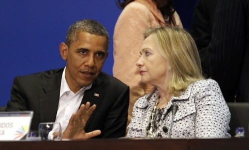 U.S. President Barack Obama and Secretary of State Hillary Clinton talk during the plenary session of the Summit of the Americas in Cartagena