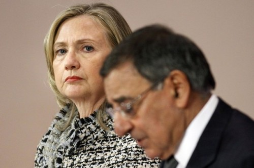 U.S. Secretary of State Clinton listens as U.S. Defense Secretary Panetta speaks during their news conference in Brussels