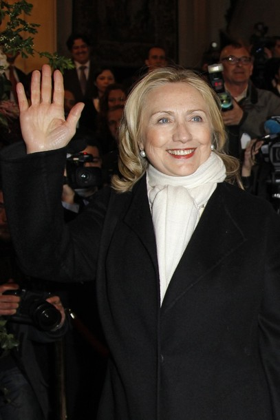 US Secretary of State Clinton waves upon her arrival to attend a meeting on Syria in Paris