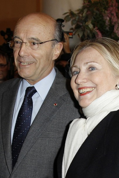US Secretary of State Clinton is greeted by French Foreign Minister Juppe upon her arrival to attend a meeting on Syria in Paris