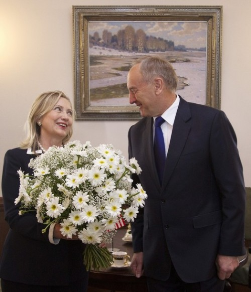 U.S. Secretary of State Hillary Rodham Clinton smiles after receiving a bouquet of flowers from Latvian President Andris Berzins before their meeting, Thursday, June 28, 2012, at the Riga Castle in Riga, Latvia. (AP Photo/Haraz N. Ghanbari, Pool)