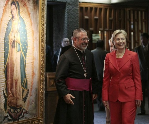 US Secretary of State Clinton smiles with priest Monrroy in front of an image of the Virgin of Guadalupe inside the Basilica de Guadalupe in Mexico City