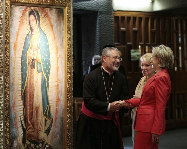 US Secretary of State Clinton shakes hands with priest Monrroy in front of an image of the Virgin of Guadalupe, inside the Basilica de Guadalupe in Mexico City