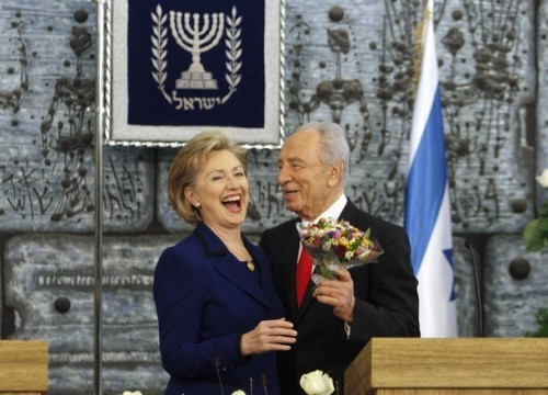 Israel's President Peres gives flowers to U.S. Secretary of State Clinton after meeting in Jerusalem