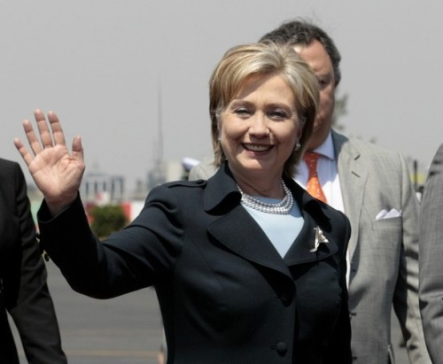 U.S. Secretary of State Hillary Clinton greets journalists as she arrives at the international airport in Mexico City