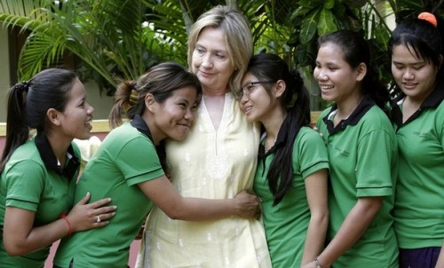 U.S. Secretary of State Hilary Clinton is greeted by human trafficking victims Van Sina and Somana at the Siem Reap AFESIP rehabilitation and vocational training center