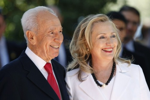 Israel's President Peres stands with U.S. Secretary of State Clinton before their meeting in Jerusalem