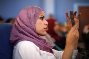 A Libyan student makes a video as U.S. Secretary of State Hillary Clinton speaks during a town hall meeting with Youth and Civil Society at Tripoli University in Libya