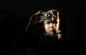 A Libyan student takes a picture while U.S. Secretary of State Hillary Clinton speaks during a town hall meeting with the Youth and Civil Society at Tripoli University in Libya