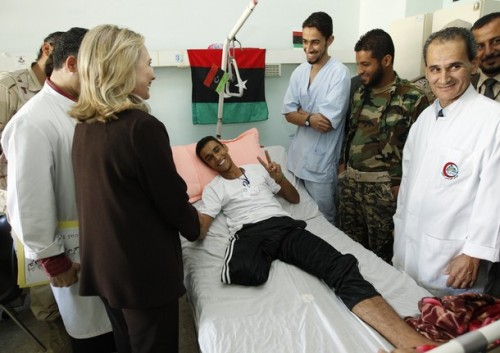 U.S. Secretary of State Hillary Clinton meets a wounded soldier at a Tripoli hospital during her visit to Libya