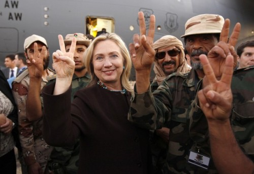 U.S. Secretary of State Hillary Clinton gestures with Libyan soldiers upon her departure from Tripoli in Libya