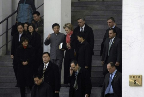 U.S. Secretary of State Clinton listens to clergy as she walks out after Sunday service in Beijing