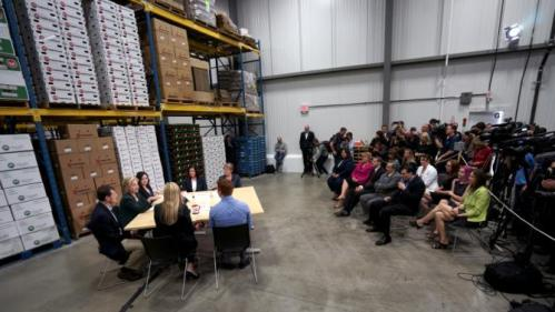 U.S. presidential candidate and former Secretary of State Hillary Clinton listens to small business owners as she campaigns for the 2016 Democratic presidential nomination at Capital City Fruit in Norfolk