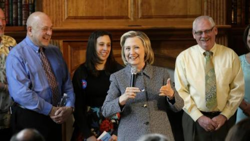 Democratic presidential candidate Hillary Rodham Clinton speaks during a gathering at the home of Dean Genth, left, and Gary Swenson, right, Monday, May 18, 2015, in Mason City, Iowa. (AP Photo/Charlie Neibergall)