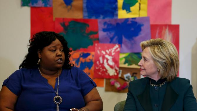 U.S. presidential candidate Hillary Clinton listens to Lakesia Collins speak at a roundtable discussion about childcare during a campaign stop in Chicago, Illinois, United States, May 20, 2015.    REUTERS/Jim Young