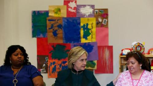 U.S. presidential candidate Hillary Clinton speaks at a roundtable discussion about childcare next to Lakesia Collins (L) and Maricarmen Macias during a campaign stop in Chicago, Illinois, United States, May 20, 2015.    REUTERS/Jim Young