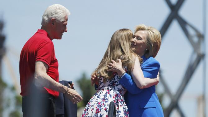 Democratic presidential candidate, former Secretary of State Hillary Rodham Clinton, right, hugs her daughter Chelsea Clinton, center, as former President Bill Clinton looks on after she spoke to supporters Saturday, June 13, 2015, on Roosevelt Island in New York. (AP Photo/Julio Cortez)
