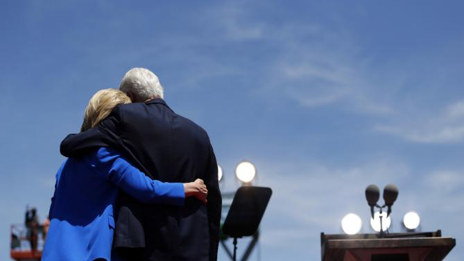 Democratic presidential candidate, former Secretary of State Hillary Rodham Clinton, left, is hugged by her husband, former President Bill Clinton, after speaking to supporters Saturday, June 13, 2015, on Roosevelt Island in New York. (AP Photo/Julio Cortez)