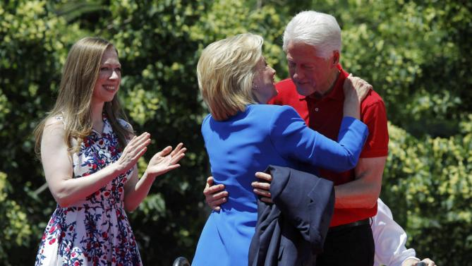 "U.S. Democratic presidential candidate Hillary Clinton hugs her husband former President Bill Clinton as their daughter Chelsea (L) looks on after Clinton delivered her ""official launch speech"" at a campaign kick off rally in Franklin D. Roosevelt Four Freedoms Park on Roosevelt Island in New York City, June 13, 2015. REUTERS/Carlo Allegri"