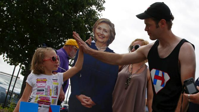"Cadence Pike (L) ""high-fives"" John West  after getting her picture taken with a life-sized cutout of U.S. Democratic presidential candidate Hillary Clinton at a campaign event in Des Moines, Iowa, United States, June 14, 2015. REUTERS/Jim Young"