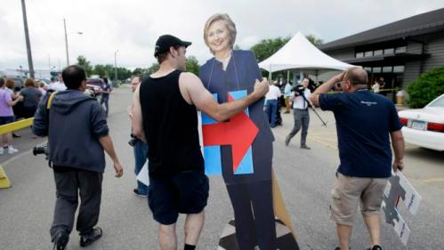 John West, of Chicago, carries a cardboard cutout of Democratic presidential candidate Hillary Rodham Clinton outside a rally, Sunday, June 14, 2015, in Des Moines, Iowa. Seeking an army of volunteers, Clinton is trying to build an organizational edge in Iowa as some of her lesser-known Democratic rivals clamor for attention in the state that tripped up her first presidential campaign. (AP Photo/Charlie Neibergall)