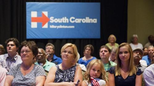 Phoebe Jordan, 8, center right, clutches a stuffed donkey while listening to Democratic presidential candidate Hillary Rodham Clinton address an audience during a campaign stop at Trident Technical College Wednesday, June 17, 2015, in North Charleston, S.C. Sitting at left is Jordan's teacher Kim Davidson with her daughter Caroline at right. (AP Photo/David Goldman)