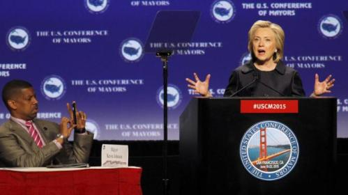 Sacramento, Calif. Mayor Kevin Johnson takes a photograph as Democratic presidential candidate Hillary Rodham Clinton speaks at the U.S. Conference of Mayors 83rd Annual Meeting as  in San Francisco, Saturday, June 20, 2015. (AP Photo/Mathew Sumner)
