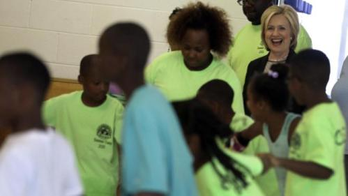Democratic presidential candidate Hillary Rodham Clinton laughs as she watches children participate in a summer camp before delivering remarks during a campaign stop at Christ the King United Church of Christ, Tuesday, June 23, 2015, in Florissant, Mo. (AP Photo/Jeff Roberson)