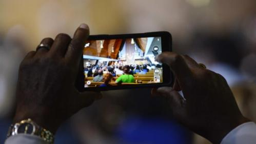 An attendee videotapes Democratic presidential candidate and former Secretary of State Hillary Clinton as she speaks about the shooting in Charleston, South Carolina and the controversy over the Confederate flag during a community meeting at Christ the King United Church of Christ as she campaigns for president in Florissant, Missouri June 23, 2015.  REUTERS/Kate Munsch