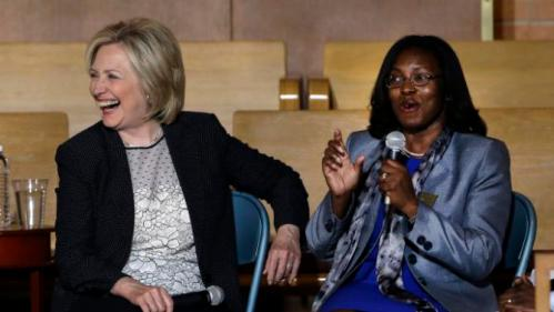Democratic presidential candidate Hillary Rodham Clinton laughs at a comment by Jennings School District Superintendent Tiffany Anderson, right, during a campaign stop at Christ the King United Church of Christ, Tuesday, June 23, 2015, in Florissant, Mo. (AP Photo/Jeff Roberson)