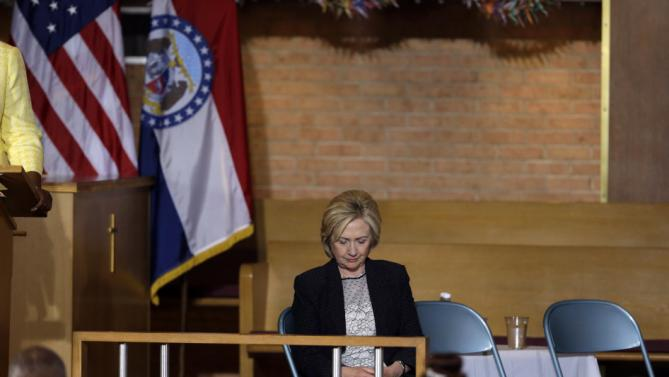 Democratic presidential candidate Hillary Rodham Clinton preys at the start of a campaign stop at Christ the King United Church of Christ, Tuesday, June 23, 2015, in Florissant, Mo. (AP Photo/Jeff Roberson)