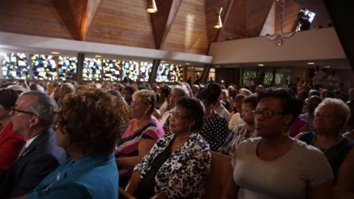 Audience members listen as Democratic presidential candidate Hillary Rodham Clinton delivers remarks during a campaign stop at Christ the King United Church of Christ, Tuesday, June 23, 2015, in Florissant, Mo. (AP Photo/Jeff Roberson)