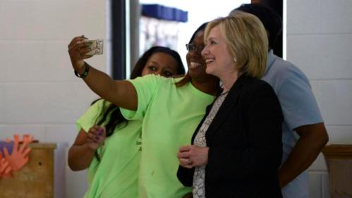 """Democratic presidential candidate and former Secretary of State Hillary Clinton poses for a """"selfie"""" with children at Christ the King United Church of Christ, as she campaigns for president in Florissant, Missouri June 23, 2015. The children are taking part of in a summer camp at the church.  REUTERS/Kate Munsch TPX IMAGES OF THE DAY"""