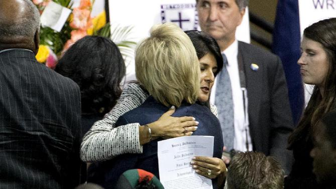 Democratic presidential candidate Hillary Rodham Clinton, left, embraces Gov. Nikki Haley at the funeral service for Rev. Clementa Pinckney, Friday, June 26, 2015, in Charleston, S.C. (AP Photo/David Goldman)