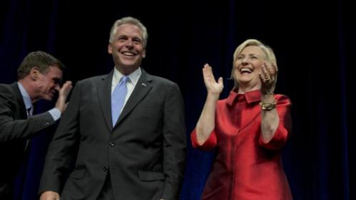 Democratic presidential candidate Hillary Rodham Clinton walks on the stage with Virginia Gov. Terry McAuliffe, center, at a Jefferson Jackson event hosted by the Democratic Party of Virginia at George Mason University's Patriot Center, in Fairfax, Va., Friday, June 26, 2015.   (AP Photo/Manuel Balce Ceneta)