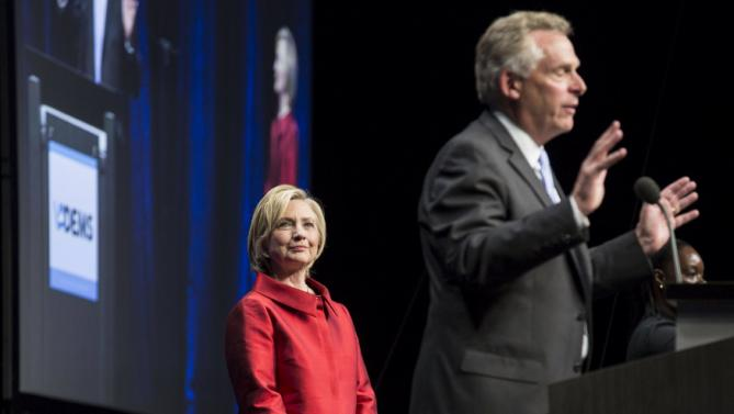 U.S. Democratic presidential candidate Hillary Clinton listens as Virginia Governor Terry McAuliffe introduces her at the Virginia Democratic Party's annual Jefferson-Jackson party fundraising dinner at George Mason University in Fairfax, Virginia, June 26, 2015.  REUTERS/Joshua Roberts