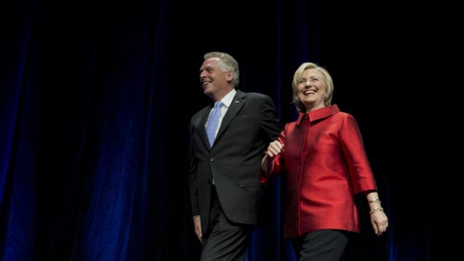 Democratic presidential candidate Hillary Rodham Clinton walks on the stage with Virginia Gov. Terry McAuliffe, left, during a Jefferson Jackson event hosted by the Democratic Party of Virginia at George Mason University's Patriot Center, in Fairfax, Va., Friday, June 26, 2015.   (AP Photo/Manuel Balce Ceneta)