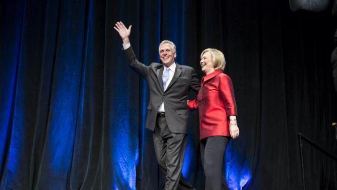 U.S. Democratic presidential candidate Hillary Clinton walks with Virginia Governor Terry McAuliffe before speaking at the Virginia Democratic Party's annual Jefferson-Jackson party fundraising dinner at George Mason University in Fairfax, Virginia, June 26, 2015. REUTERS/Joshua Roberts