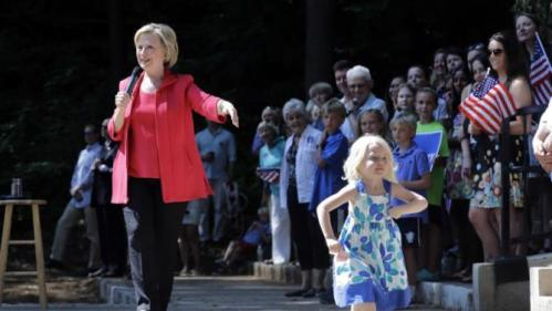 Louisa Hill, 3, front right, walks onto the stage as Democratic presidential candidate Hillary Rodham Clinton speaks during a campaign event, Friday, July 3, 2015, in Hanover, N.H. (AP Photo/Elise Amendola)