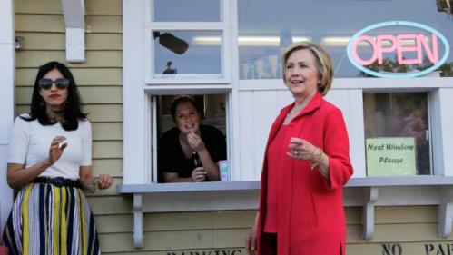 Democratic presidential candidate Hillary Rodham Clinton, right, and her personal aide Huma Abedin offer to buy ice cream for reporters from Allison Porreca at Dairy Twirl, Friday, July 3, 2015, in Lebanon, N.H. (AP Photo/Elise Amendola)