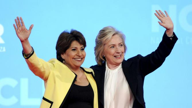U.S. Democratic Presidential candidate and former U.S. Secretary of State Hillary Clinton waves to the audience with Janet Murguia, the president and CEO of La Raza (L), during the National Council of La Raza annual conference in Kansas City, Missouri July 13, 2015. REUTERS/Dave Kaup
