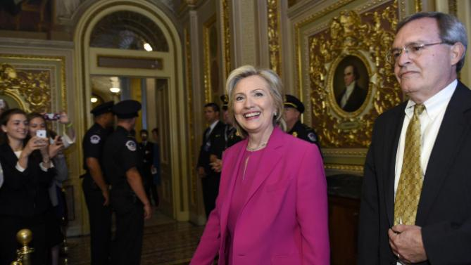 Democratic presidential candidate Hillary Rodham Clinton, center, walks with David McCallum, Deputy Chief of Staff for Senate Minority Leader Sen. Harry Reid of Nev., right, as they arrive for the weekly policy luncheon with Senate Democrats on Capitol Hill in Washington, Tuesday, July 14, 2015. Clinton is on Capitol Hill meeting with House and Senate Democrats. (AP Photo/Susan Walsh)