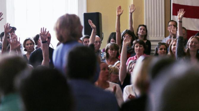 Audience guests raise their hands to ask a question to Democratic presidential candidate Hillary Rodham Clinton as she addresses a gathering during a town hall meeting in Dover, N.H., Thursday, July 16, 2015. (AP Photo/Charles Krupa)
