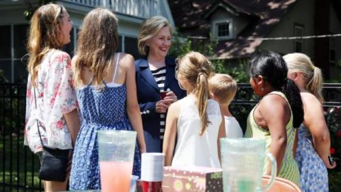 Presidential hopeful Hillary Clinton stops at a lemonade stand outside her event in Beaverdale, Iowa, for a glass of pink lemonade on Saturday, July 25, 2015. Clinton spoke to a crowd of people and then stuck around to answer questions and shake hands with those who attended. (Kelsey Kremer/The Des Moines Register via AP)