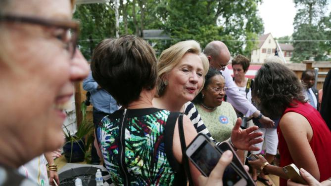 Presidential hopeful Hillary Clinton shakes hands, gives hugs and poses for photos with attendees of her campaign event on Saturday, July 25, 2015 in the backyard of a Beaverdale, Iowa, home.  (Kelsey Kremer/The Des Moines Register via AP)
