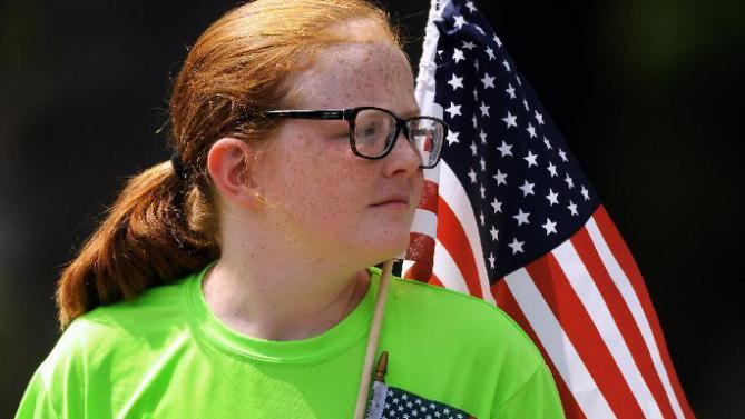 A young Hillary Rodham Clinton supporter holds two U.S. flags on Wednesday, July 29, 2015, in the Green Ridge section of Scranton, Pa., where Clinton spoke during a private fundraiser at the home of long time supporter Virginia McGregor on Wednesday, July 29, 2015.  ( Butch Comegys / The Scranton Times-Tribune via AP)  MANDATORY CREDIT