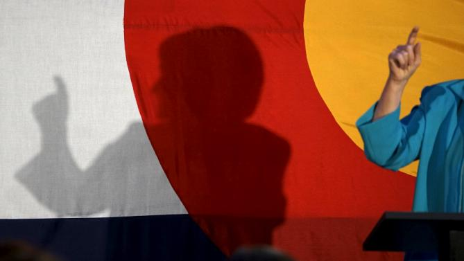 Democratic presidential candidate Hillary Clinton addresses supporters as she casts a shadow on a giant Colorado flag at an event in Denver, Colorado August 4, 2015.  REUTERS/Rick Wilking