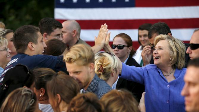 U.S. Democratic presidential candidate Hillary Clinton high-fives a supporter at a campaign stop in Manchester, New Hampshire, August 10, 2015.   REUTERS/Brian Snyder